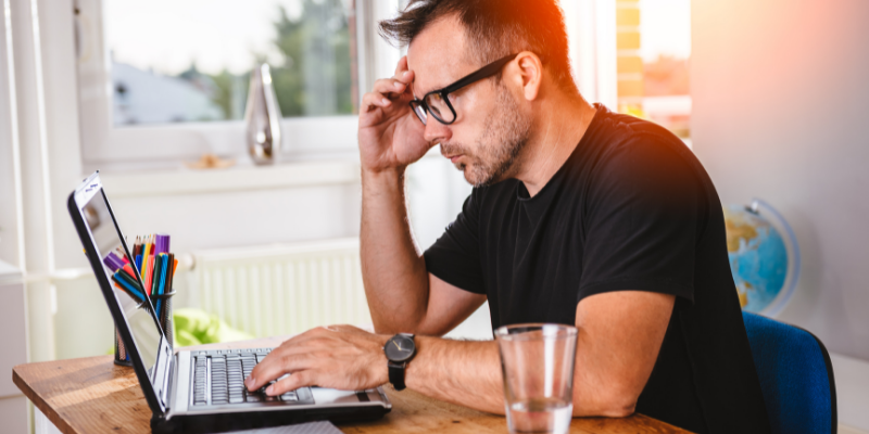 Man with glasses working on computer, for Is Final Draft a One-Time Purchase