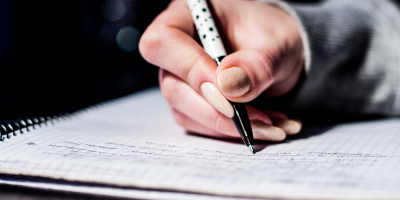 Hand with a pen writing on paper—What is a Non-Specific Word Choice