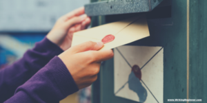 A woman's hands putting a letter into a post office box—How To Write a Letter to an Author